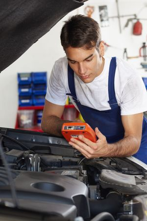 manual test equipment: mechanic leaning on bonnet with tester equipment and looking at camera Stock Photo