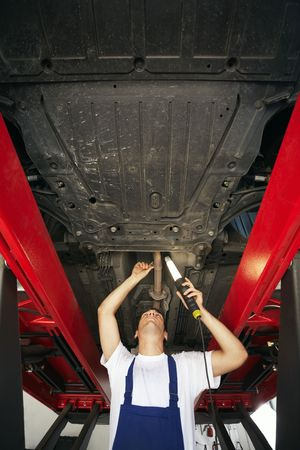 mechanic standing under car engine and holding lamp. Copy space photo