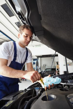 oil change: side view of mechanic checking motor oil. Selective focus on hand and dipstick Stock Photo