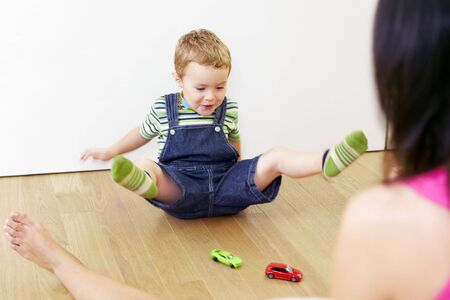 adult toys: mother and son sitting on floor and playing with toy cars.