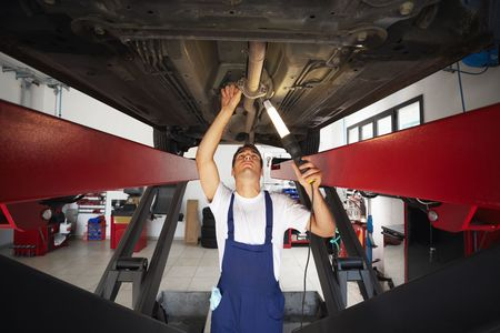 motor mechanic: mechanic standing under car engine and holding lamp. Copy space Stock Photo