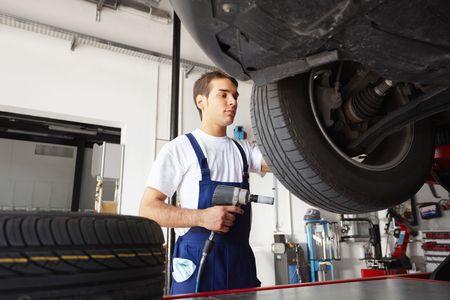 llantas: mec�nico de la sustituci�n de los neum�ticos de coches en taller de reparaci�n de autom�viles. �ngulo bajo vista Foto de archivo