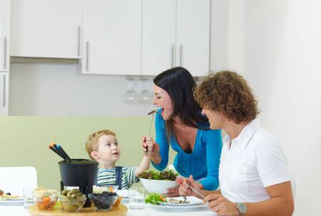 happy family eating meat fondue at home. Copy space photo