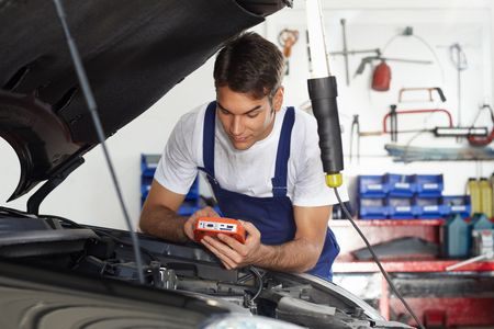 manual test equipment: mechanic leaning on bonnet with tester equipment