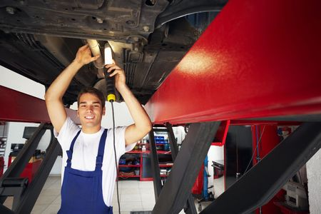 shop skill: portrait of mechanic standing under car and looking at camera. Copy space