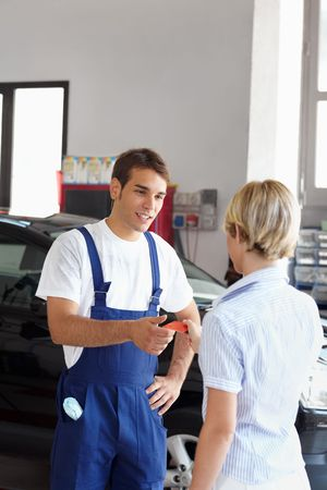 Rear view of woman giving credit card to mechanic. Copy space photo