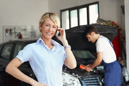 portrait of female client talking on mobile phone in auto repair shop. photo