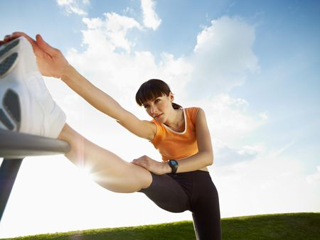 растягивание: woman doing stretching outdoors at sunset. Low angle view, copy space