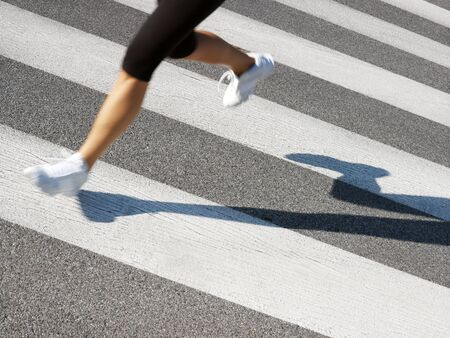 cropped out: cropped view of female runner crossing street. Copy space