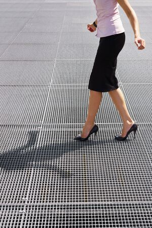 business woman legs: side view of business woman balancing on high heels. Copy space