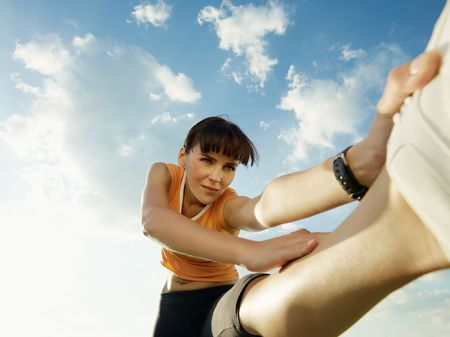 woman doing stretching outdoors at sunset. Low angle view, copy space photo