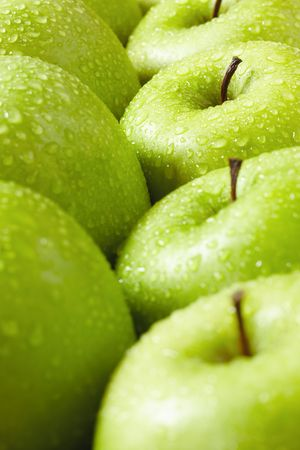 fruit drop: large group of granny smith apples in a row. Selective focus