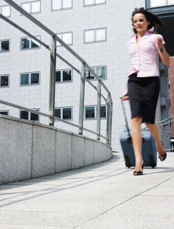 business woman rushes out of the office with trolley bag Stock Photo