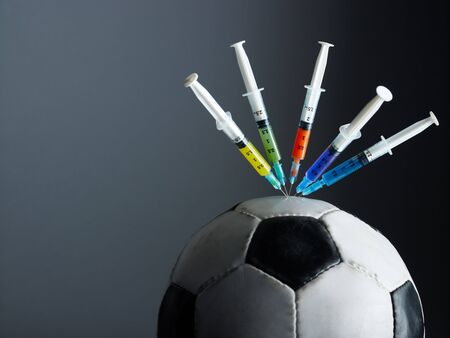 five syringes threaded in soccer ball. Copy space photo