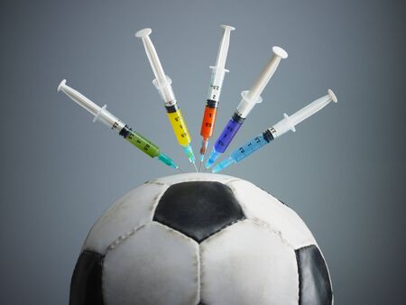medicine ball: five syringes threaded in soccer ball. Copy space