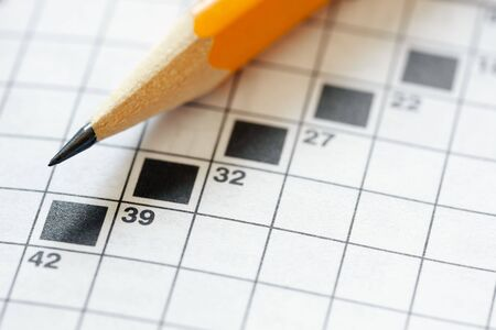 Close up of pencil on crossword puzzle. Copy space photo