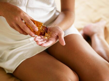cropped view of young woman holding pills. High angle view Stock Photo - 5486174