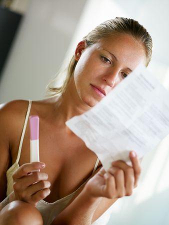 test de grossesse: blonde femme tenant un test de grossesse et de la lecture de l'information. Banque d'images