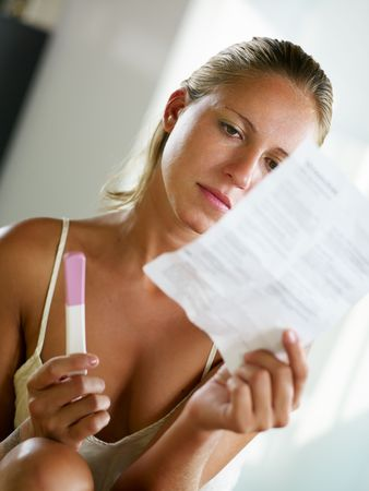 blonde woman holding pregnancy test and reading information. photo