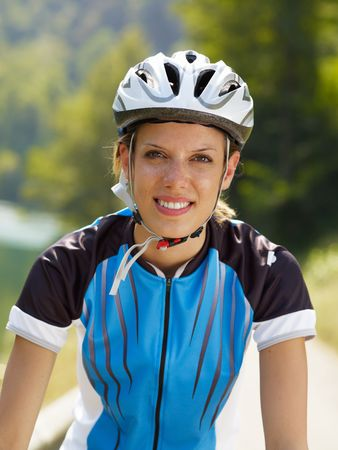 young woman with bicycle helmet, looking at camera photo