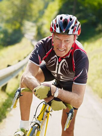 senior man leaning on road bike, looking at camera.