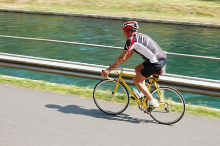 road bike: Senior bicyclist on road bike. Blurred background. Copy space Stock Photo