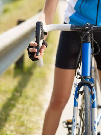 bicyclists: Cropped view of female cyclist with hands on brakes. Copy space