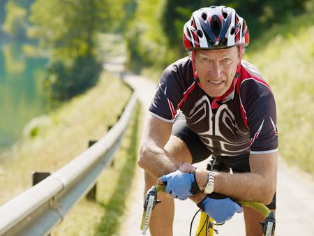 senior man leaning on road bike, looking at camera. photo