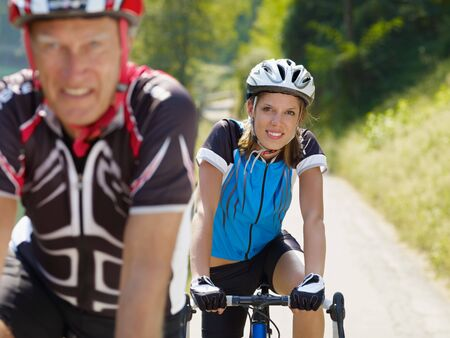 road bike: Senior man and young woman on road bike. Focus on background