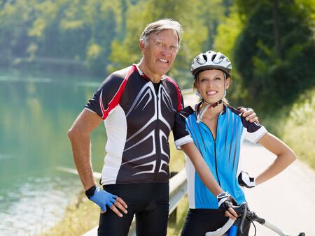 road bike: Senior man and young woman on road bike. Copy space Stock Photo
