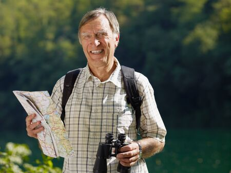 bird watcher: senior hiker holding map and binoculars and looking at camera. Copy space Stock Photo