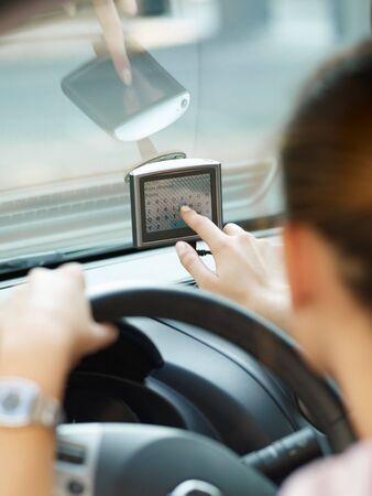 steering: Rear view of woman typing on gps. Selective focus