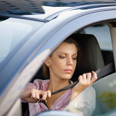 safety belt: woman in car fastening safety belt Stock Photo