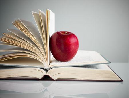 libros abiertos: pila de libros y la manzana roja sobre la mesa. Copiar el espacio