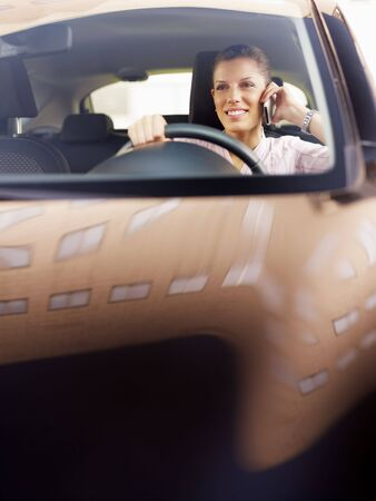 woman driving car and talking on mobile phone. Copy space photo