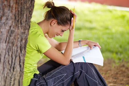 young woman studying outdoors and leaning on tree photo