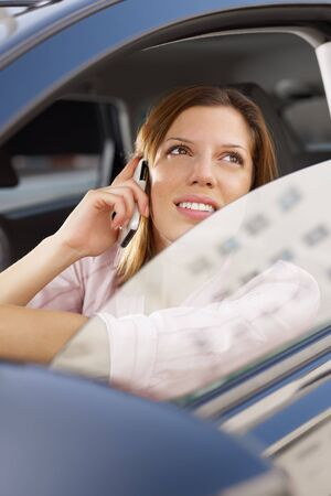 woman driving car and talking on mobile phone.  photo