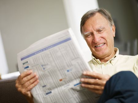 listings: Senior man reading stock listings and smiling. Copy space Stock Photo