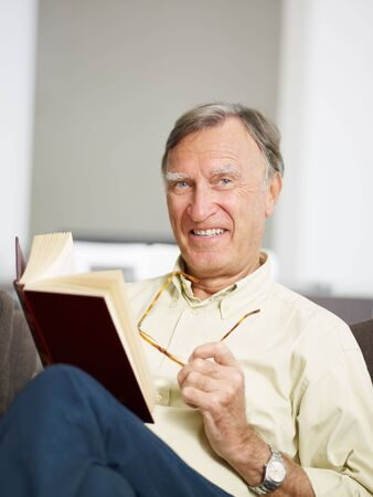 senior man reading book at home and looking at camera. Copy space Stock Photo - 5652348