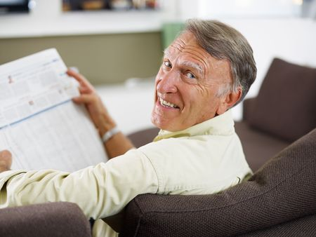 over shoulders: senior man reading newspaper at home and looking over shoulders  Stock Photo