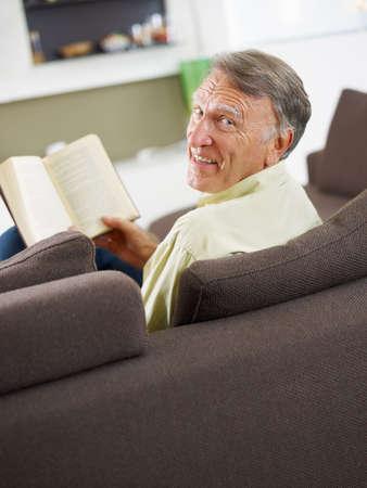 everyday scenes: libro di lettura senior l'uomo a casa e guardando oltre le spalle Archivio Fotografico