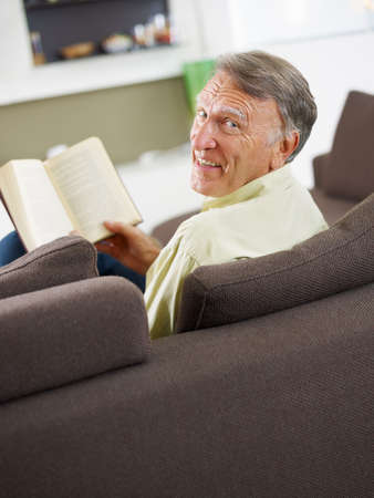 one senior adult man: senior man reading book at home and looking over shoulders  Stock Photo