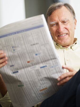 everyday scenes: Senior man reading stock listings and smiling