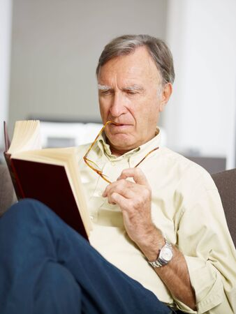 senior man reading book at home photo