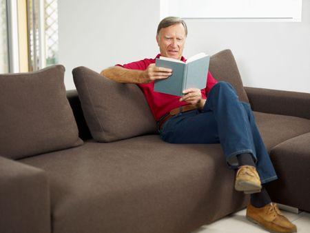 everyday scenes: libro di lettura senior l'uomo a casa e sorridente