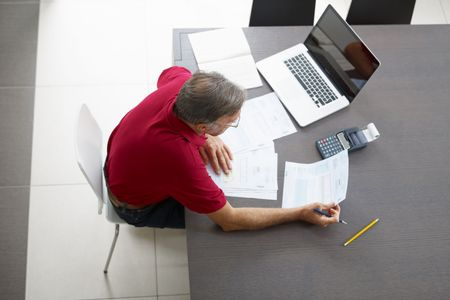 everyday scenes: Senior man checking home finances. High angle view