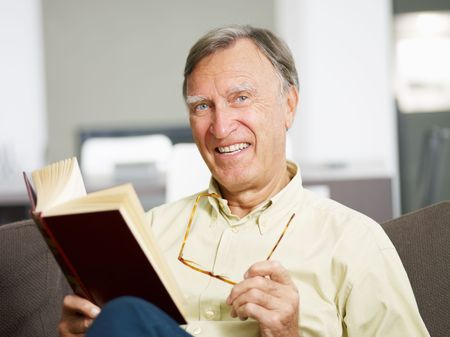 senior man reading book at home and looking at camera. Copy space Stock Photo - 5677514