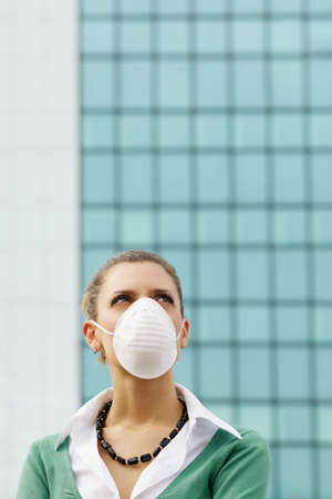 woman standing against office building and wearing protective mask. Copy space photo