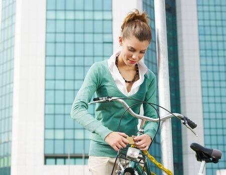 city bike: female commuter locking padlock to her bike. Copy space Stock Photo