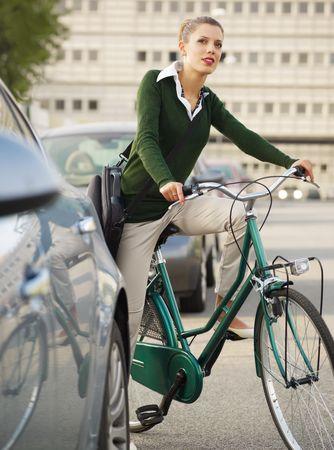 cyclist: vrouw op fiets woon-werkverkeer en weg kijken